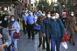 People wearing protective face masks to help prevent spread of the coronavirus walk on a sidewalk of a commercial street in Tehran, Iran, Sunday, Sept. 20, 2020. Iran's president dismissed U.S. efforts to restore all U.N. sanctions on the country as mounting economic pressure from Washington pushed the local currency down to its lowest level ever on Sunday. (AP Photo/Vahid Salemi)