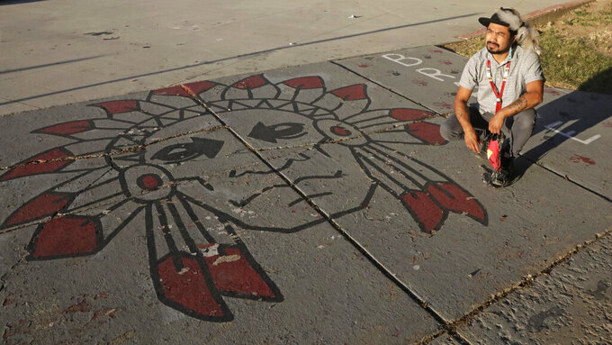 Native American advocate Carl Moore sits next to Native American imagery painted along a walkway which leads from the Bountiful High School parking lot up to the football field Tuesday, July 28, 2020, in Bountiful, Utah. While advocates have made strides in getting Native American symbols and names changed in sports, they say there's still work to do mainly at the high school level, where mascots like Braves, Indians, Warriors, Chiefs and Redskins persist. (AP Photo/Rick Bowmer)