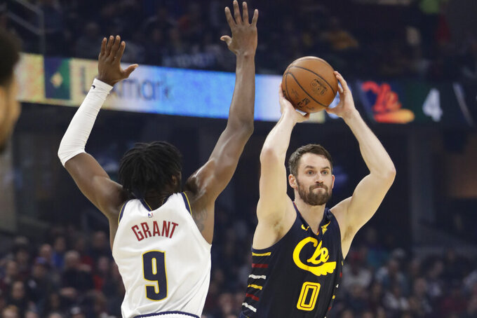 File-This March 7, 2020, file photo shows Cleveland Cavaliers' Kevin Love (0) passing against Denver Nuggets' Jerami Grant (9) in the first half of an NBA basketball game, in Cleveland. The NBA's interrupted season and invitation-only gathering in Florida to finish it due to the pandemic hurt every team to varying degrees. It devastated the Cleveland Cavaliers.(AP Photo/Tony Dejak, File)