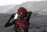 In this Oct. 23, 2019, photo, a laborer smiles as he prepares to drink water during a break from loading coal into trucks for transportation in the village of Godhar in Jharia, a remote corner of eastern Jharkhand state, India. The fires started in coal pits in eastern India in 1916. More than a century later, they are still spewing flames and clouds of poisonous fumes into the air, forcing residents to brave sizzling temperatures, deadly sinkholes and toxic gases. (AP Photo/Aijaz Rahi)