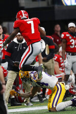 Georgia running back D'Andre Swift (7) jumps over LSU cornerback Derek Stingley Jr. (24) during the first half of the Southeastern Conference championship NCAA college football game, Saturday, Dec. 7, 2019, in Atlanta. (AP Photo/John Bazemore)