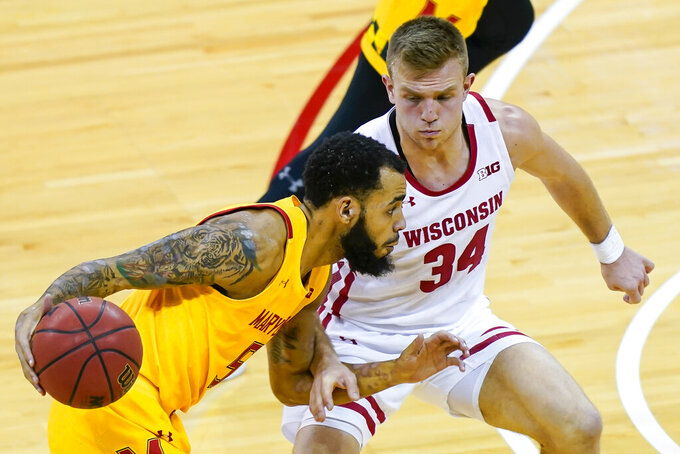 Maryland's Eric Ayala (5) drives against Wisconsin's Brad Davison (34) during the first half of an NCAA college basketball game Tuesday, Jan. 14, 2020, in Madison, Wis. (AP Photo/Andy Manis)