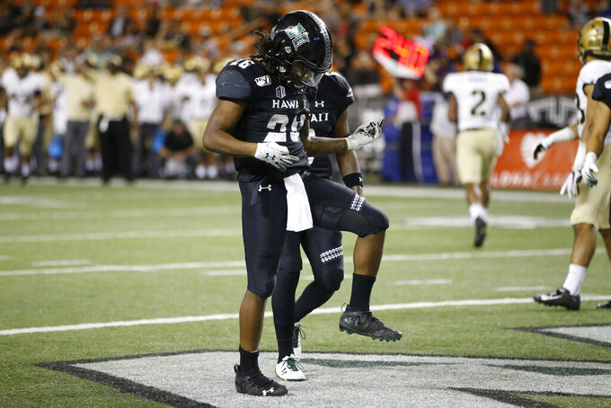 Hawaii running back Miles Reed (26) reacts after making a touchdown in the end zone against Army during the second half of an NCAA college football game Saturday, Nov. 30, 2019 in Honolulu. (AP Photo/Marco Garcia)