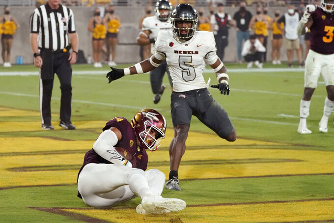 Arizona State wide receiver Johnny Wilson (14) pulls in a touchdown as UNLV defensive back Phillip Hill (5) pursues during the first half of an NCAA college football game, Saturday, Sept. 11, 2021, in Tempe, Ariz. (AP Photo/Matt York)