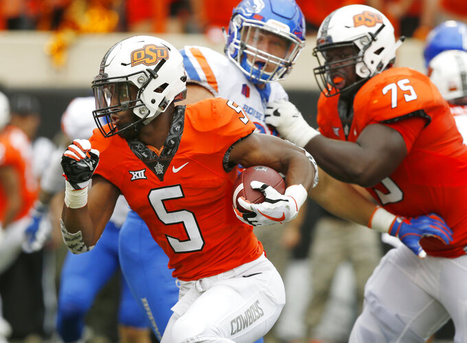 FILE - In this Sept. 15, 2018, file photo, Oklahoma State running back Justice Hill (5) runs past Boise State defensive end Durrant Miles, center, and teammate Marcus Keyes (75) and into the endzone with a touchdown in the first half of an NCAA college football game, in Stillwater, Okla. This season, four Big 12 backs are averaging at least 100 yards rushing per game in conference action. (AP Photo/Sue Ogrocki, File)