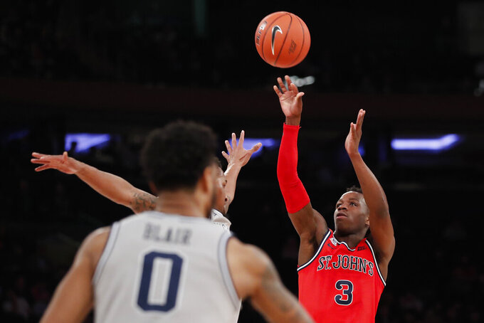 St. John's guard Rasheem Dunn (3) shoots as Georgetown guard Jahvon Blair (0) watches during the second half of an NCAA college basketball game in the first round of the Big East men's tournament Wednesday, March 11, 2020, in New York. St. John's defeated Georgetown, 75-62. (AP Photo/Kathy Willens)