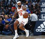 New York Knicks forward Marcus Morris Sr., front, picks up the ball as Denver Nuggets forward Torrey Craig defends in the second half of an NBA basketball game Sunday, Dec. 15, 2019, in Denver. (AP Photo/David Zalubowski)