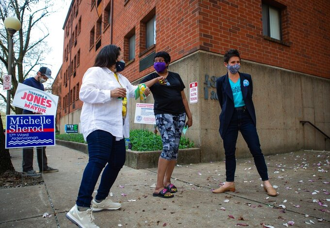 Mayoral Candidate Cara Spencer, right, and Aldermanic Candidate Michelle Sharod, (front left, in white) greet voter Karen Morrow outside the polling place at the corner of Newstead and Laclede Avenues in the Central West End in St. Louis on Tuesday, April 6, 2021. (Sara Diggins/St. Louis Post-Dispatch via AP)