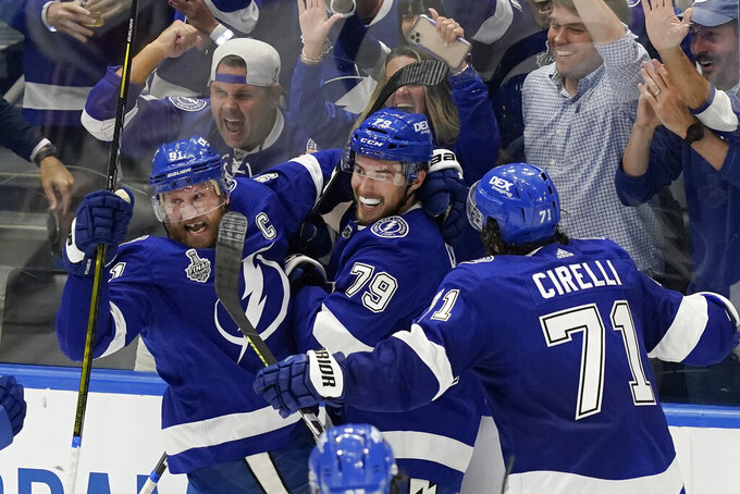 Tampa Bay Lightning center Steven Stamkos, left, and center Anthony Cirelli (71) crowd left wing Ross Colton (79) after scoring on Montreal Canadiens goaltender Carey Price during the second period in Game 5 of the NHL hockey Stanley Cup finals, Wednesday, July 7, 2021, in Tampa, Fla. (AP Photo/Gerry Broome)