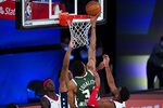 Milwaukee Bucks' Giannis Antetokounmpo (34) tips in a rebound against the Washington Wizards during the first half of an NBA basketball game, Tuesday, Aug. 11, 2020, in Lake Buena Vista, Fla. (AP Photo/Ashley Landis, Pool)
