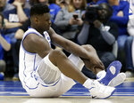 FILE - In this Wednesday, Feb. 20, 2019, file photo, Duke's Zion Williamson sits on the floor following an injury during the first half of an NCAA college basketball game against North Carolina, in Durham, N.C. As his Nike shoe blew out, Williamson sprained his right knee on the first possession of what became top-ranked Duke's 88-72 loss to No. 8 North Carolina. (AP Photo/Gerry Broome, File)