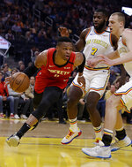 Houston Rockets' Russell Westbrook, left, drives the ball against Golden State Warriors' Eric Paschall (7) and Alen Smailagic, right, during the first half of an NBA basketball game Thursday, Feb. 20, 2020, in San Francisco. (AP Photo/Ben Margot)