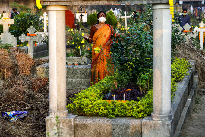 An Indian Christian woman wearing a face mask as a precaution against the coronavirus prays beside the grave of a deceased relative during All Souls Day in Kolkata, India, Monday, Nov. 2, 2020. (AP Photo/Bikas Das)