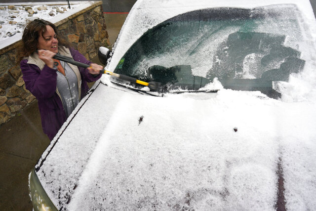 Diane Lee cleans the windshield of her sports-utility vehicle as she heads home after a day at her job with the Clear Creek County Sheriff's Department while a storm packing high winds and snow sweeps through the intermountain West Tuesday, Sept. 8, 2020, in Georgetown, Colo. Forecasters predict that the storm will continue through Wednesday before moving out on to the plains. (AP Photo/David Zalubowski)