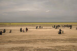 In this Wednesday, March 6, 2019, photo, women and children walk to a reception area for people evacuated from the last shred of territory held by Islamic State militants, outside Baghouz, Syria. (AP Photo/Gabriel Chaim)