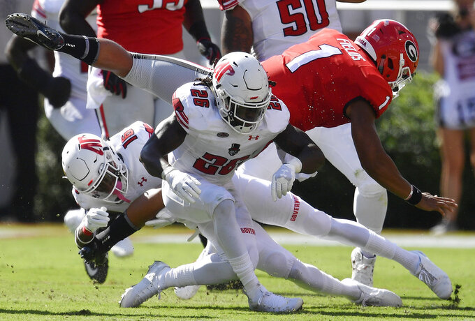 Georgia quarterback Justin Fields (1) is hit by Austin Peay defensive back Juantarious Bryant (26) during the first half of an NCAA college football game, Saturday, Sept. 1, 2018, in Athens, Ga. (AP Photo/Mike Stewart)