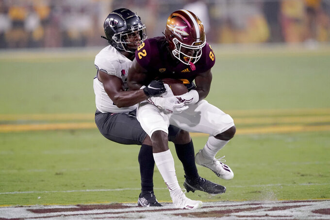 UNLV defensive back Aaron Lewis tackles Arizona State wide receiver Andre Johnson (82) during the first half of an NCAA college football game, Saturday, Sept. 11, 2021, in Tempe, Ariz. (AP Photo/Matt York)