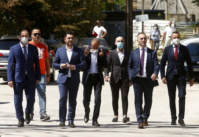 Lawmakers and candidates for ministers of the ethnic Albanian DUI party walk towards the parliament building in Skopje, North Macedonia, Sunday, Aug. 30, 2020. North Macedonia's parliament continues Sunday the debate on a vote of confidence for a new left-wing coalition government after the Social Democrats and their ethnic Albanian partners secured a majority of seats in July's general election. (AP Photo/Boris Grdanoski)