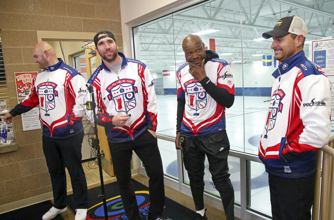 In this Jan. 3, 2019 photo, former Minnesota Vikings football player Jared Allen, second from left, stands with his three curling teammates, from left, Michael Roos, Keith Bullock and Marc Bulger after practice for a competition in Blaine, Minn. Allen retired from NFL football in 2015 and wasn't ready to give up on the competition he'd come to enjoy as a five-time All-Pro in a 12-year career. His solution: Make it to the 2022 Olympics _ in curling. Less than a year later, he and the three who have never curled before will attempt to qualify for the U.S. championships against curlers who have been throwing stones for most of their lives. (AP Photo/Jim Mone)