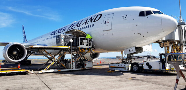 In this photo released by Air New Zealand, an Air New Zealand Boeing 777-300 is loaded with luggage ahead of its departure for Frankfurt via Vancouver at the Auckland International Airport in New Zealand, Friday, April 3, 2020. About 100,000 tourists stuck in New Zealand since it started a coronavirus lockdown last week are starting to fly home Friday and the flight is expected to land at Frankfurt Main Airport early morning on Saturday 4 April. (Air New Zealand via AP)