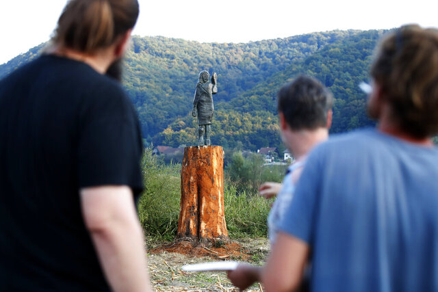 Local people look at a bronze statue representing the U.S first lady Melania Trump made by Brad Downey, a Berlin-based U.S. artist, is erected in her birthplace of Sevnica, Slovenia, Tuesday, Sept. 15, 2020, after a previous one, made in wood, was set alight. Melania Trump was born and grew up in Slovenia before moving abroad as a fashion model. (AP Photo)