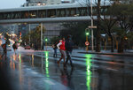 People cross a road in a stormy Cape Town, South Africa, Friday, May 29, 2020. With dramatically increased community transmissions, Cape Town has become the center of the coronavirus outbreak in South Africa. (AP Photo/Nardus Engelbrecht)