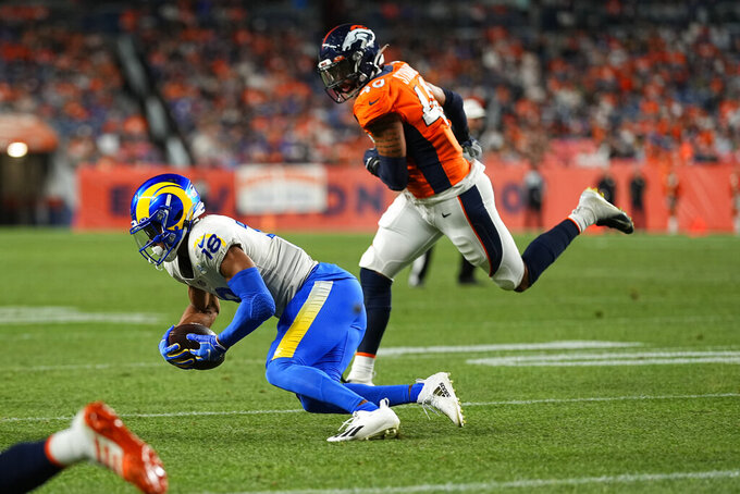 Los Angeles Rams wide receiver Jeremiah Haydel (18) makes a catch as Denver Broncos linebacker Justin Strnad (40) defends during the second half of an NFL preseason football game, Saturday, Aug. 28, 2021, in Denver. (AP Photo/Jack Dempsey)