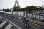 Parisians ride their bikes along the Seine river in Paris, Sunday, May 24, 2020 as France gradually lifts its COVID-19 lockdown. In the French capital this weekend, Parisians soaked up the sun along the embankments of the Seine River and lounged on ledges outside the Tuileries Gardens, still shuttered like all of the city's parks as the city gradually emerges from confinement. (AP Photo/Francois Mori)