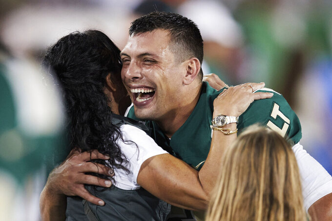 Charlotte quarterback Chris Reynolds, right, is congratulated by fans following a win over Duke in an NCAA college football game on Friday, Sept. 3, 2021, in Charlotte, N.C. (AP Photo/Brian Westerholt)