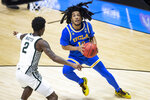 UCLA's Tyger Campbell (10) looks for a shot as Michigan State's Rocket Watts (2) defends during the second half of a First Four game in the NCAA men's college basketball tournament, early Friday, March 19, 2021, at Mackey Arena in West Lafayette, Ind. UCLA won 86-80. (AP Photo/Robert Franklin)