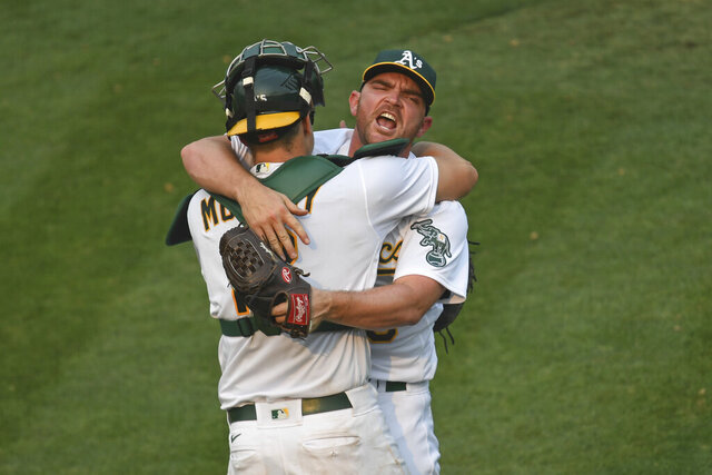Oakland Athletics pitcher Liam Hendriks celebrates with catcher Sean Murphy after striking out Chicago White Sox's Nomar Mazara for the final out of Game 3 of an American League wild-card series, Thursday, Oct. 1, 2020, in Oakland, Calif. The A's won 6-4. (Jose Carlos Fajardo//Bay Area News Group via AP)