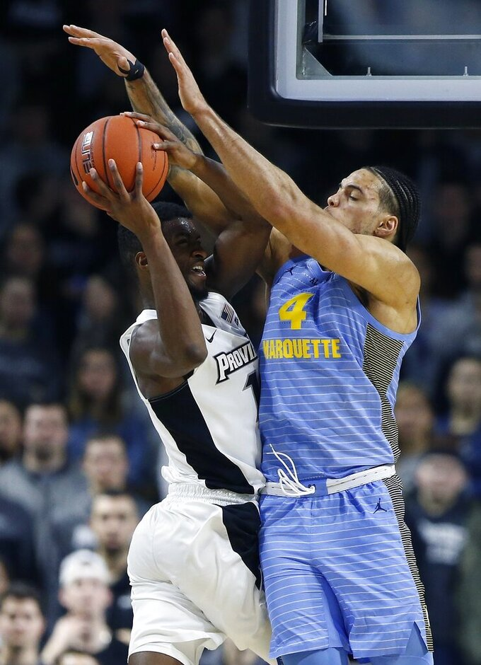 Marquette's Theo John (4) blocks a shot by Providence's Alpha Diallo during the second half of an NCAA college basketball game in Providence, R.I., Saturday, Feb. 23, 2019. (AP Photo/Michael Dwyer)