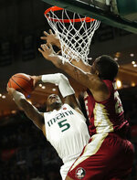 Miami guard Zach Johnson (5) attempts to shoot against Florida State forward Mfiondu Kabengele (25) during the first half of an NCAA college basketball game, Sunday, Jan. 27, 2019, in Coral Gables, Fla. (AP Photo/Wilfredo Lee)