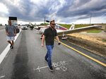 The driver, right, of a black Acura that was struck by a small plane, background, making an emergency landing on the eastbound ramp of Maitland Blvd. to Interstate 4, walks to his car to retrieve personal belongings. Thursday, May 16, 2019, in Maitland, Fla. (Joe Burbank/Orlando Sentinel via AP)
