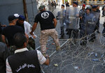Lebanese retired soldiers, left, step on the barbed wires, as they try to enter the parliament building where lawmakers and ministers are discussing the draft 2019 state budget, in Beirut, Lebanon, Friday, July 19, 2019.  The budget is aimed at averting a financial crisis in heavily indebted Lebanon. But it was met with criticism for failing to address structural problems. Instead, the budget mostly cuts public spending and raises taxes. (AP Photo/Hussein Malla)