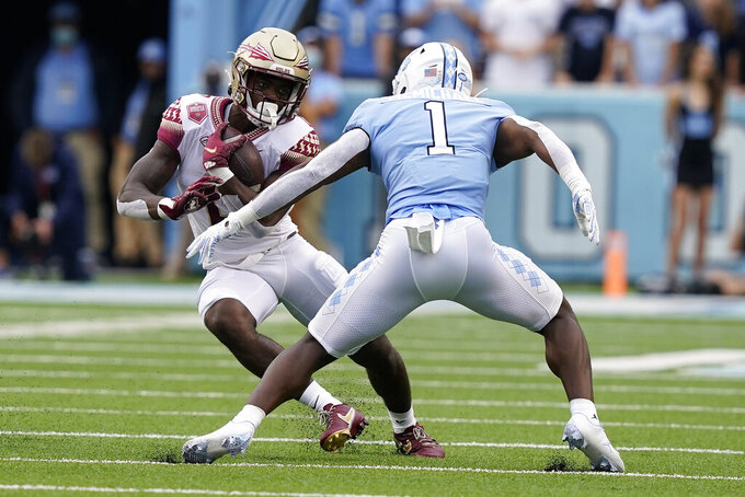 Florida State running back Jashaun Corbin (0) runs the ball while North Carolina defensive back Kyler McMichael (1) looks for the tackle during the first half of an NCAA college football game in Chapel Hill, N.C., Saturday, Oct. 9, 2021. (AP Photo/Gerry Broome)