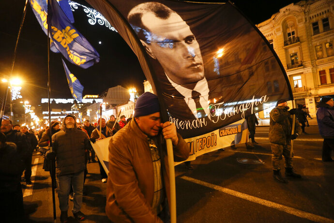 Activists of various nationalist parties carry torches and a portrait of Stepan Bandera during a rally in Kyiv, Ukraine, Wednesday, Jan. 1, 2020. The rally was organized to mark the birth anniversary of Stepan Bandera, founder of a rebel army that fought against the Soviet regime and who was assassinated in Germany in 1959. (AP Photo/Efrem Lukatsky)