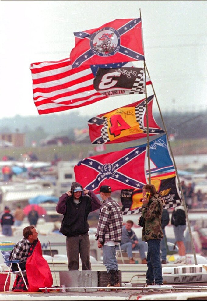 FILE - In this April 26, 1997, file photo, race fans huddle against a bitter wind at the Talladega Superspeedway during the rain-delayed NASCAR Busch series auto race in Talladega, Ala. Bubba Wallace, the only African-American driver in the top tier of NASCAR, calls for a ban on the Confederate flag in the sport that is deeply rooted in the South. (AP Photo/Dave Martin, File)