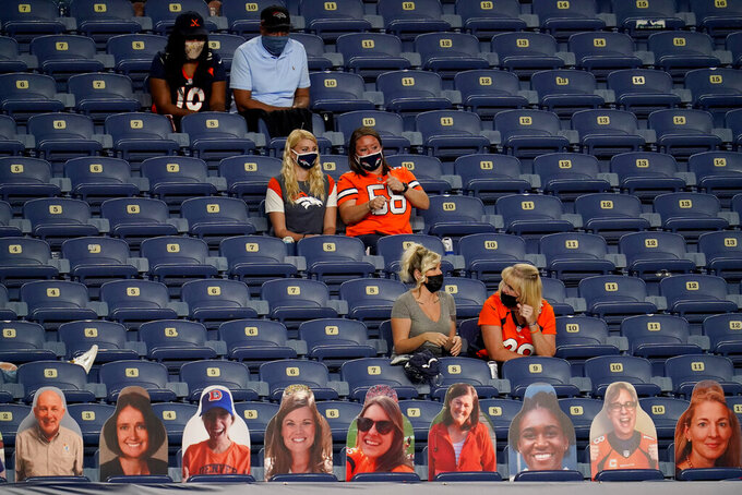 Socially distanced friends and family of players watch the Denver Broncos and the Tennessee Titans compete during the first half of an NFL football game, Monday, Sept. 14, 2020, in Denver. (AP Photo/David Zalubowski)