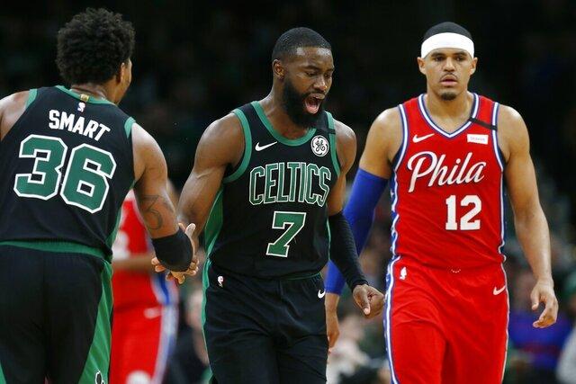 Boston Celtics' Jaylen Brown (7) celebrates with teammate Marcus Smart (36) after scoring as Philadelphia 76ers' Tobias Harris (12) walks upcourt during the second half of an NBA basketball game in Boston, Saturday, Feb. 1, 2020. (AP Photo/Michael Dwyer)