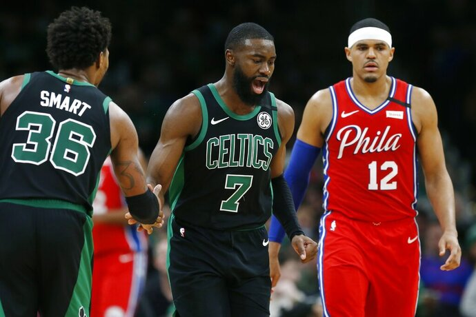 Boston Celtics' Jaylen Brown (7) celebrates with teammate Marcus Smart (36) after scoring as Philadelphia 76ers' Tobias Harris (12) walks upcourt during the second half of an NBA basketball game in Boston, Saturday, Feb. 1, 2020. (AP Photo/Michael Dwyer)