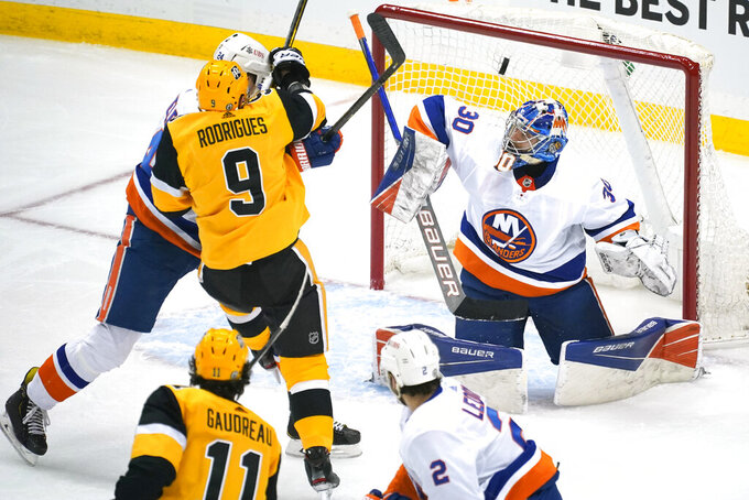 Pittsburgh Penguins' Frederick Gaudreau (11) puts a shot over New York Islanders goaltender Ilya Sorokin (30) for a goal during the first period of Game 1 of an NHL hockey Stanley Cup first-round playoff series in Pittsburgh, Sunday, May 16, 2021. (AP Photo/Gene J. Puskar)