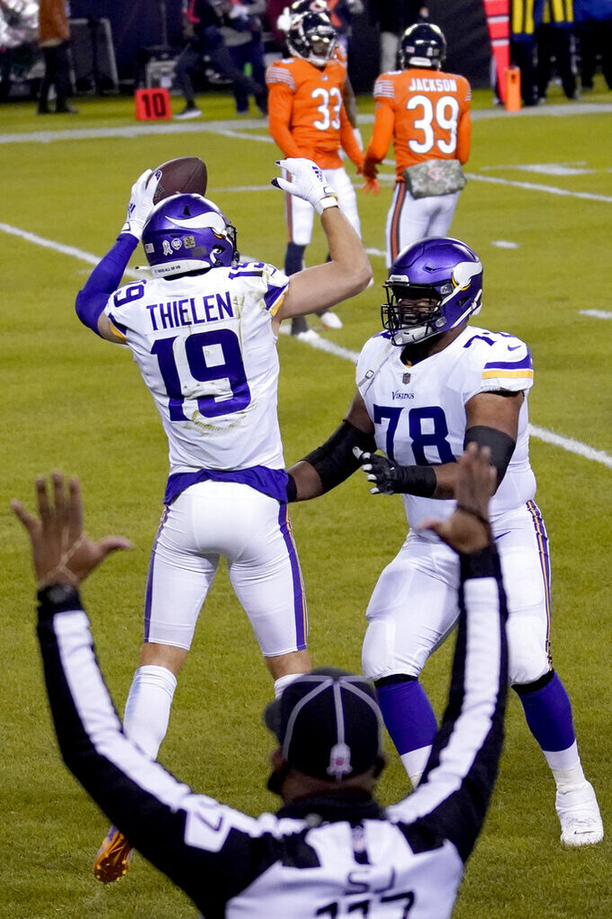 Minnesota Vikings wide receiver Adam Thielen (19) celebrates with guard Dakota Dozier (78) after catching a touchdown pass during the first half of an NFL football game against the Chicago Bears Monday, Nov. 16, 2020, in Chicago. (AP Photo/Charles Rex Arbogast)
