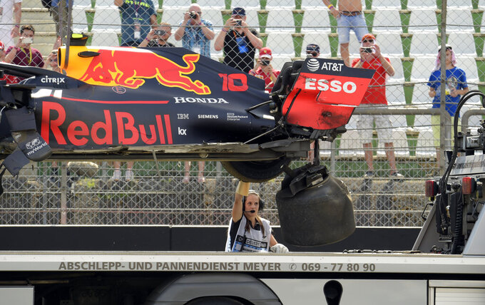 The car of Red Bull driver Pierre Gasly of France is lifted onto a flatbead after his car hit a barrier during the second Formula One practice session at the Hockenheimring racetrack in Hockenheim, Germany, Friday, July 26, 2019. The German Formula One Grand Prix will be held on Sunday. (AP Photo/Jens Meyer)