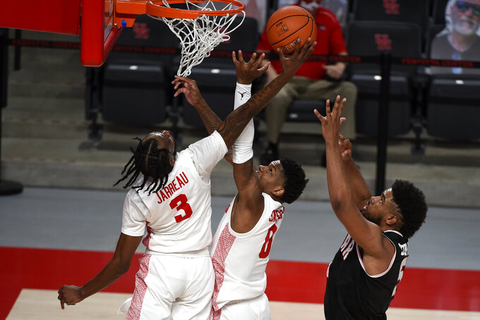 Houston guard DeJon Jarreau (3) grabs a rebound over guard Marcus Sasser, center, and Lamar forward Avery Sullivan, right, during the first half of an NCAA college basketball game, Wednesday, Nov. 25, 2020, in Houston. (AP Photo/Eric Christian Smith)