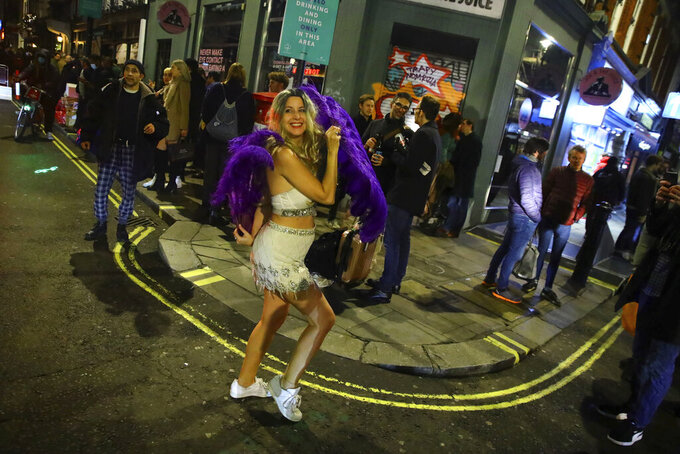 A woman dances with purple feathers in the West End of London after pubs close, before London moves into the highest tier of coronavirus restrictions from Wednesday as a result of soaring case rates, Tuesday Dec. 15, 2020. (Aaron Chown/PA via AP)