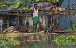 A flood affected family stands on a banana raft near their submerged house in Burgaon, east of Gauhati, Assam, India, Monday, July 15, 2019. After causing flooding and landslides in Nepal, three rivers are overflowing in northeastern India and submerging parts of the region, affecting the lives of more than 2 million, officials said Monday. (AP Photo/Anupam Nath)