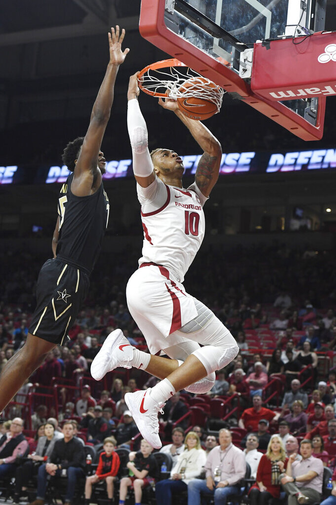 Arkansas forward Daniel Gafford, right, dunks the ball over Vanderbilt defender Clevon Brown, left, during the first half of an NCAA college basketball game, Tuesday, Feb. 5, 2019 in Fayetteville, Ark. (AP Photo/Michael Woods)