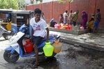 An Indian boy arranges plastic vessels filled with drinking water on his scooter at a water distribution point, which are replenished by water tankers, in Chennai, capital of the southern Indian state of Tamil Nadu, Wednesday, June 19, 2019. Millions of people are turning to water tank trucks in the state as house and hotel taps run dry in an acute water shortage caused by drying lakes and depleted groundwater. Some private companies have asked employees to work from home and several restaurants are closing early and even considering stopping lunch meals if the water scarcity aggravates. (AP Photo/R. Parthibhan)