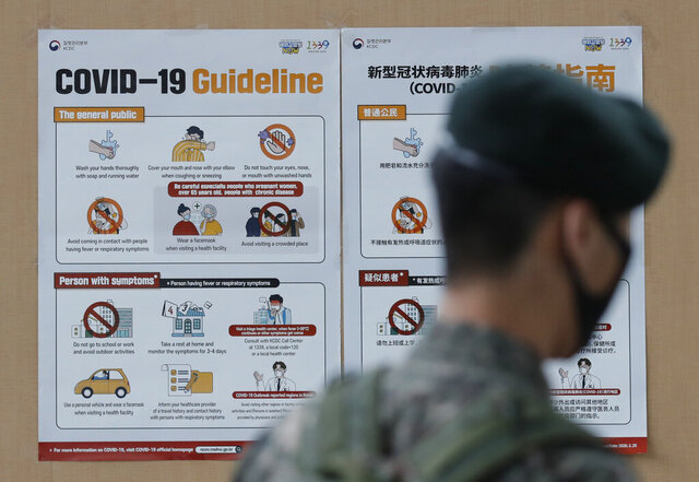 A South Korean soldier wearing a face mask walks near banners showing precautions against the new coronavirus in Seoul, South Korea, Wednesday, June 17, 2020. (AP Photo/Lee Jin-man)